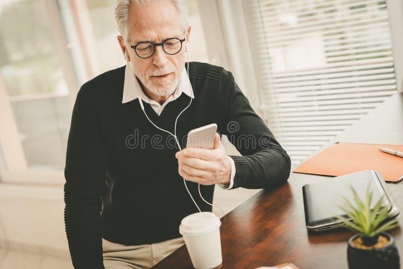 Affärsman som använder hörlurar under konversation på mobiltelefonen royaltyfri bild