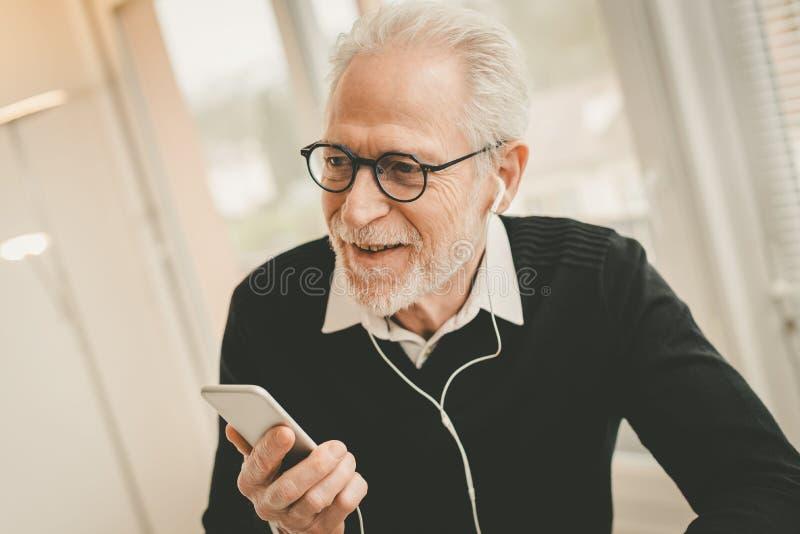 Affärsman som använder hörlurar under konversation på mobiltelefonen arkivfoto