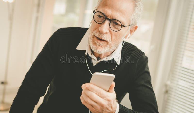 Affärsman som använder hörlurar under konversation på mobiltelefonen royaltyfria foton