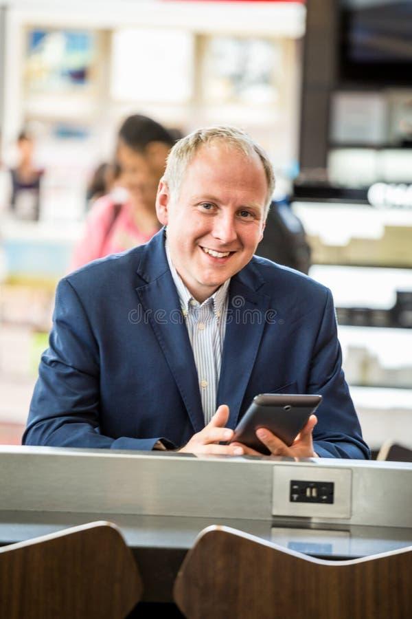 Affärsman som använder hans minnestavla på flygplatsen arkivbilder
