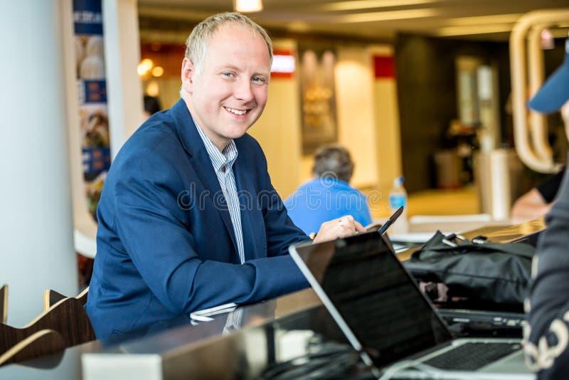 Affärsman som använder hans minnestavla på flygplatsen fotografering för bildbyråer