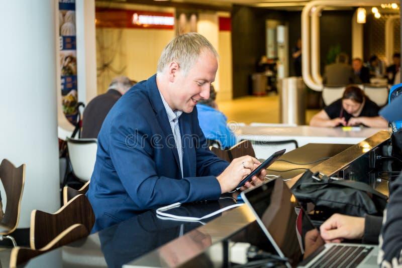 Affärsman som använder hans minnestavla på flygplatsen arkivfoton
