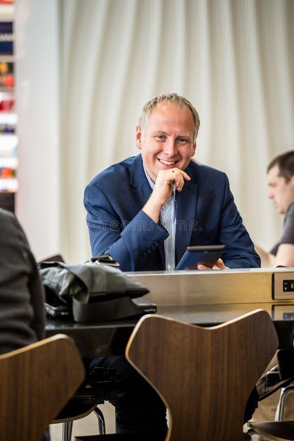 Affärsman som använder hans minnestavla på flygplatsen royaltyfria bilder