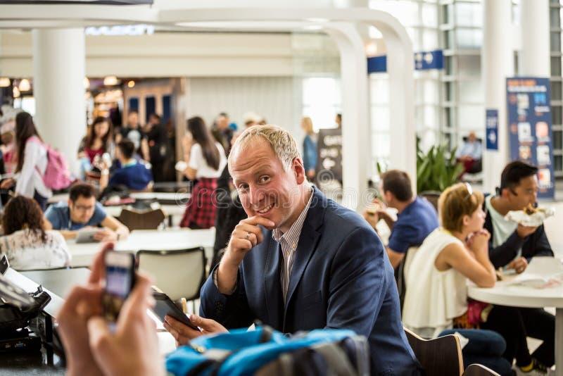 Affärsman som använder hans minnestavla på flygplatsen royaltyfri fotografi