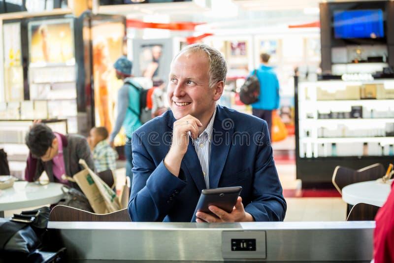 Affärsman som använder hans minnestavla på flygplatsen royaltyfria foton
