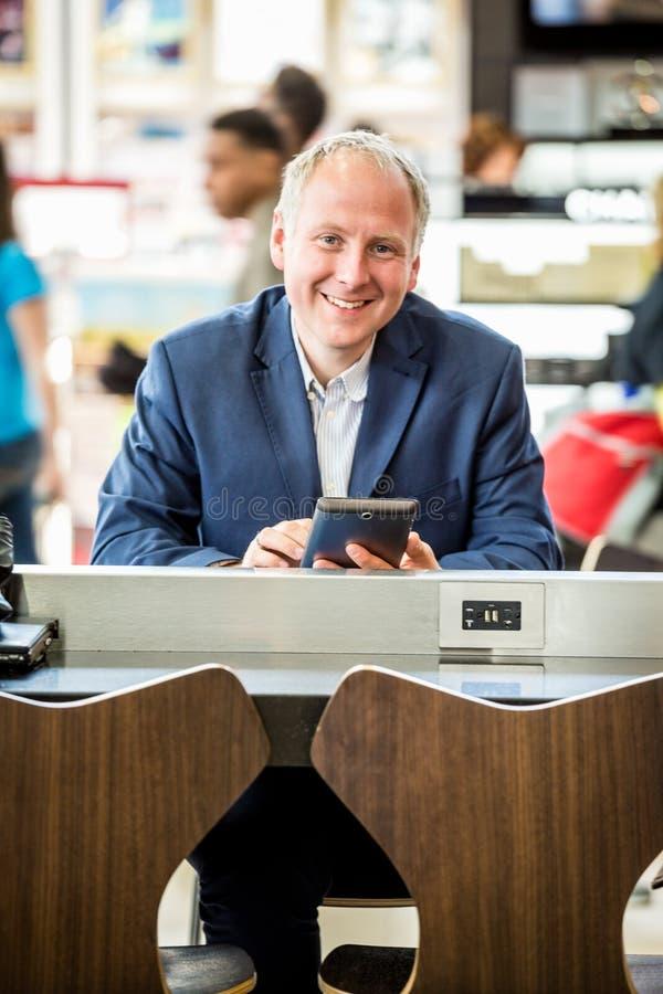 Affärsman som använder hans minnestavla på flygplatsen arkivfoto