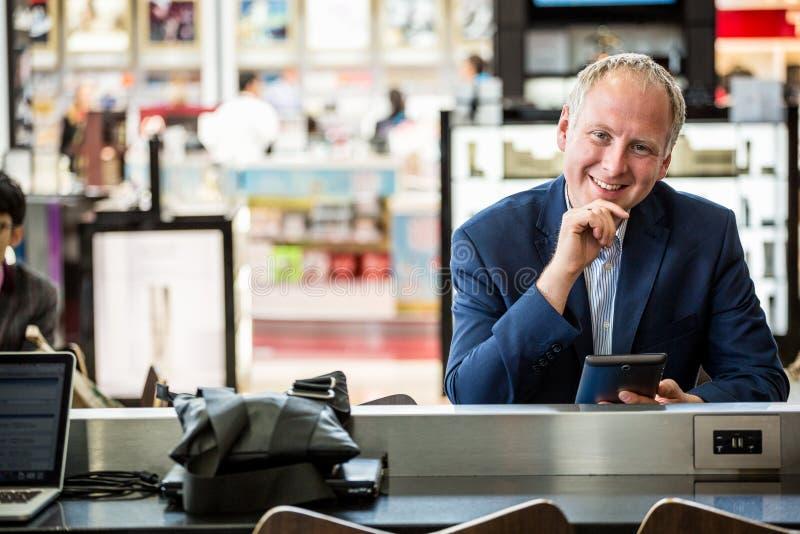 Affärsman som använder hans minnestavla på flygplatsen royaltyfri bild
