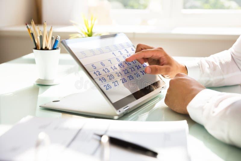 Affärsman som använder kalendern på bärbara datorn royaltyfri foto