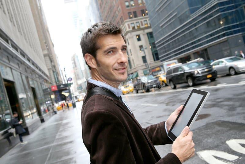 Affärsman som använder minnestavlan i gatorna av New York royaltyfri foto