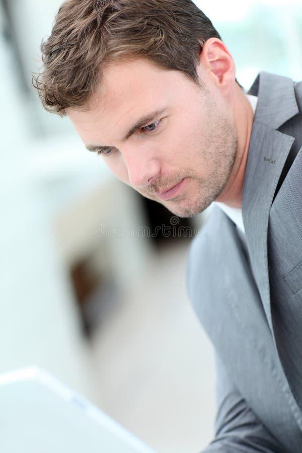 Affärsman som använder minnestavlan i korridoren royaltyfri fotografi