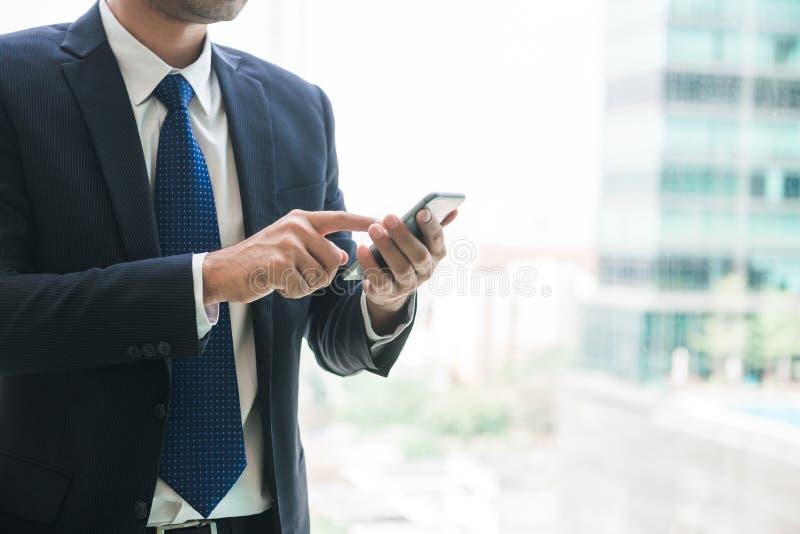 Affärsman som använder mobiltelefonen app som förutom smsar kontoret i stads- stad med skyskrapabyggnader i bakgrunden arkivbild