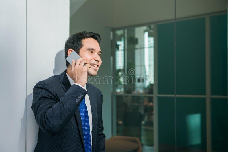 Affärsman som använder mobiltelefonen app som förutom smsar kontoret i stads- stad med skyskrapabyggnader i bakgrunden royaltyfri fotografi