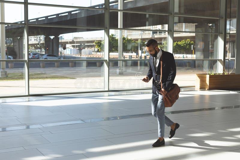 Affärsman som använder mobiltelefonen, medan gå i lobbykontor royaltyfri foto