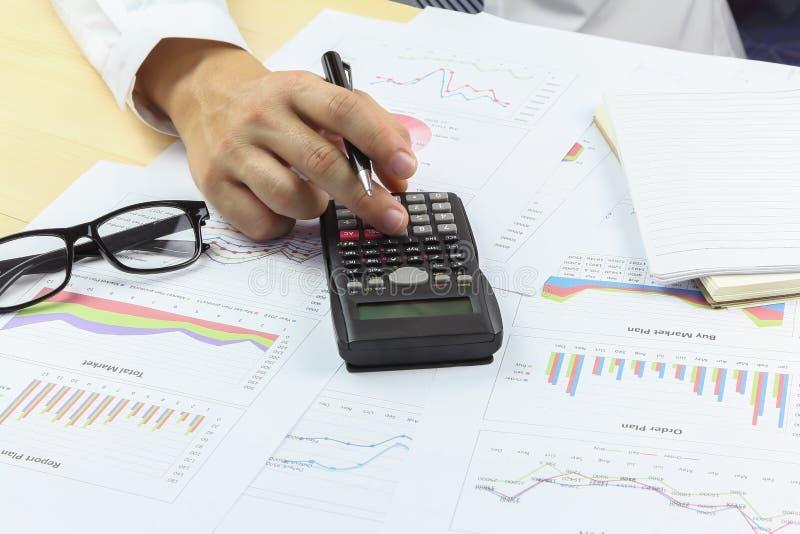 Affärsman som använder räknemaskinen med affärsgrafen som analyserar summa arkivbilder