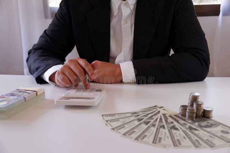 Affärsman som använder räknemaskinen med mynt och pengar över skrivbordet royaltyfria foton