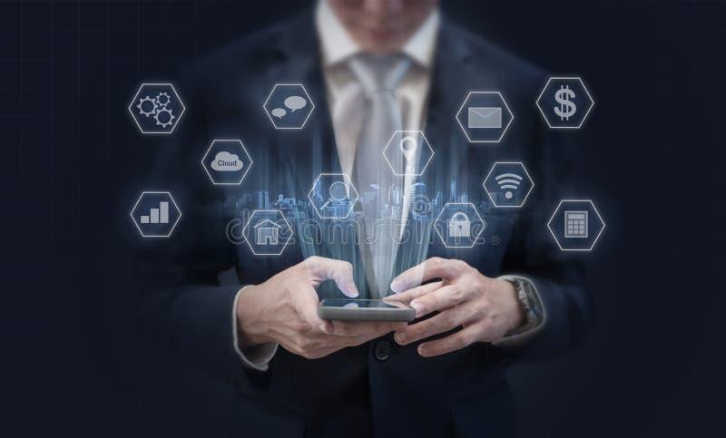 Affärsman som använder smarta telefon- och applikationsymboler för mobil Mobil applikation, socialt massmedia och e-kommers tekno arkivbild
