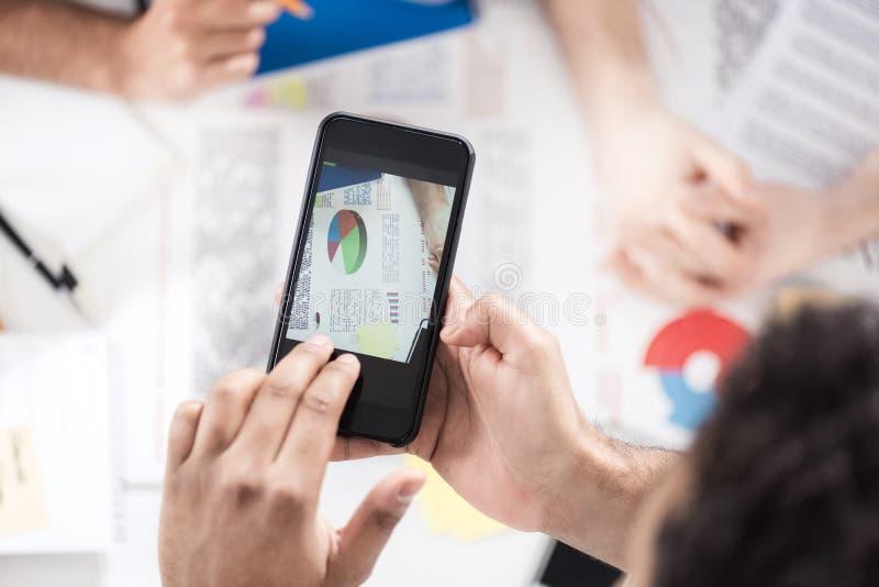 Affärsman som använder smartphonen, medan sitta på skrivbordet med legitimationshandlingar och arbete med kollegor arkivbilder