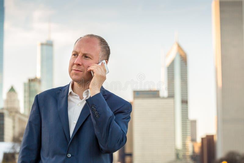 Affärsman som använder telefonen utanför kontoren royaltyfri foto