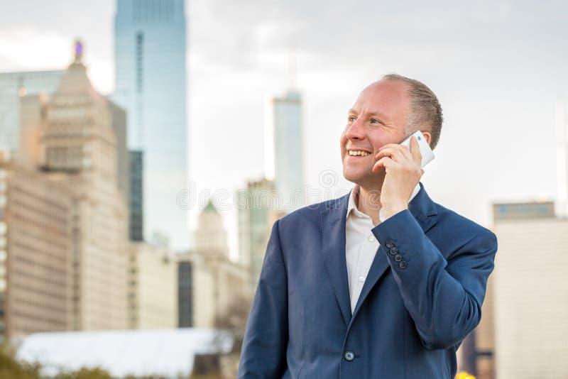 Affärsman som använder telefonen utanför kontoren arkivbilder