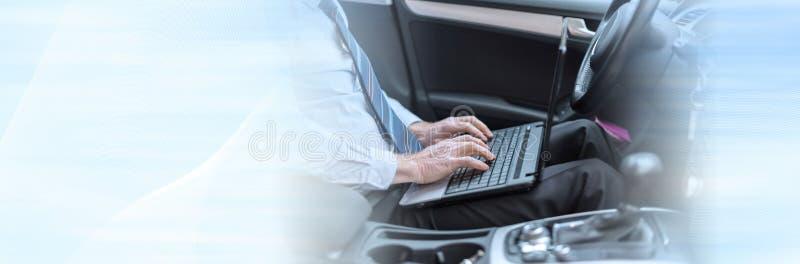 Affärsman som arbetar i hans bil panorama- baner arkivbild