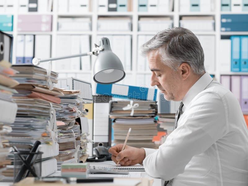 Affärsman som arbetar i kontoret och högarna av skrivbordsarbete royaltyfria foton