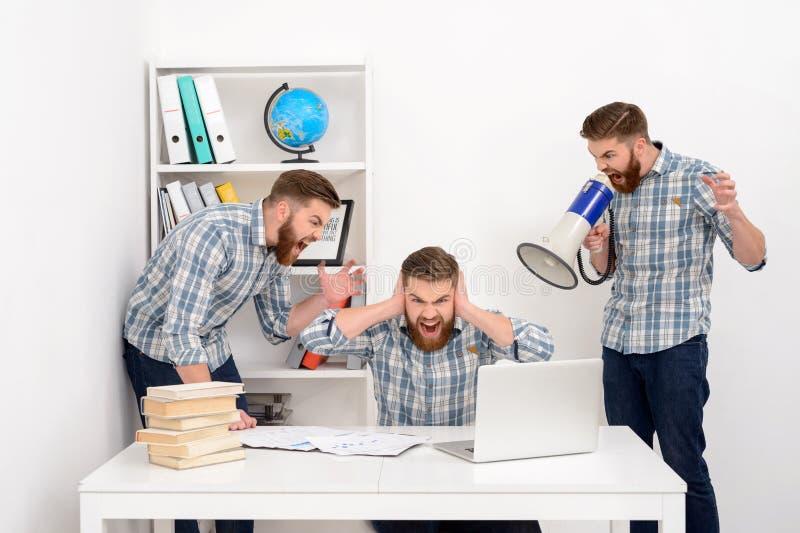Affärsman som arbetar med åtskilliga klon av honom på kontoret royaltyfria foton