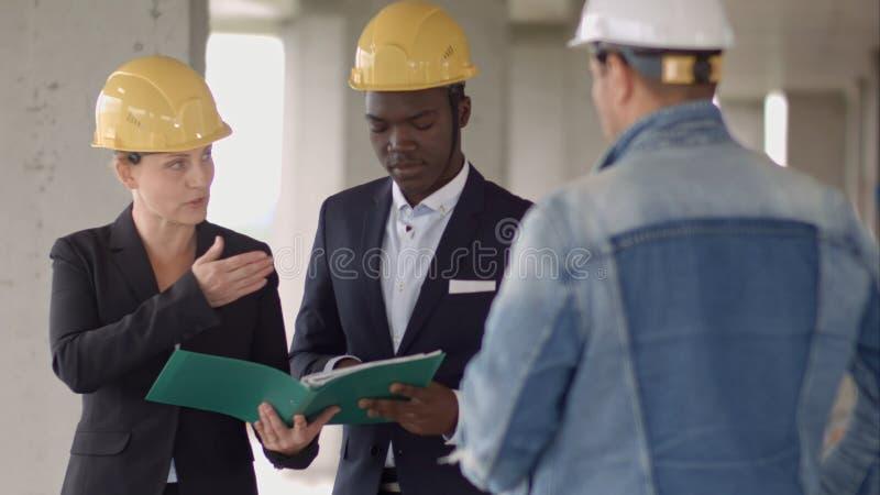 Affärsman som arbetar med arkitekten Engineer i byggnadskonstruktionsplats med ritningen som kontrollerar plan royaltyfri fotografi