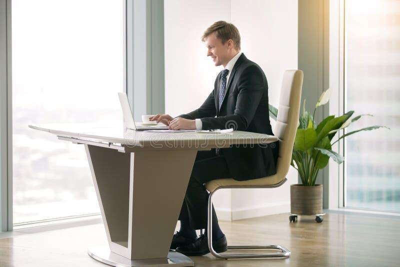 Affärsman som arbetar med bärbara datorn på modermskrivbordet royaltyfria foton
