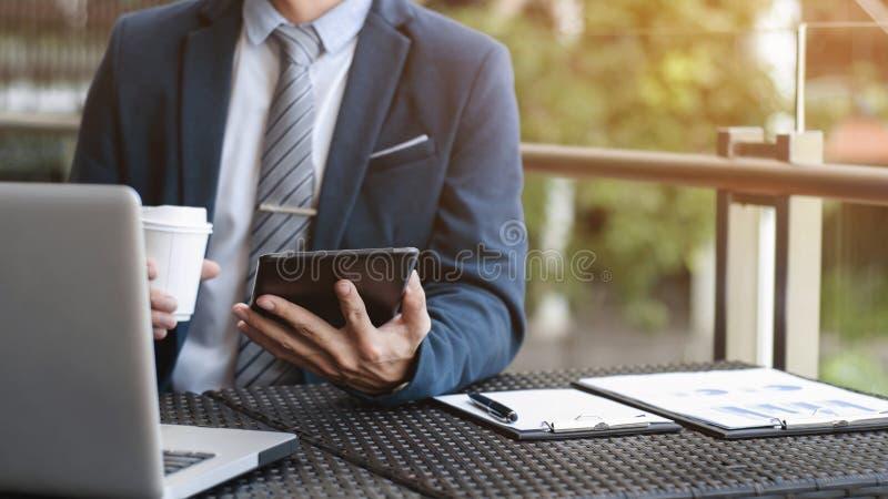 Affärsman som arbetar med den digitala minnestavlan och bärbara datorn med finansiell affärsstrategi på ett coffee shopkafé arkivbilder