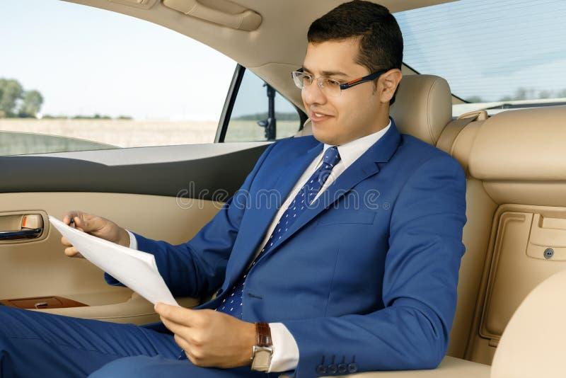 Affärsman som arbetar med legitimationshandlingar i backseat av bilen arkivbild