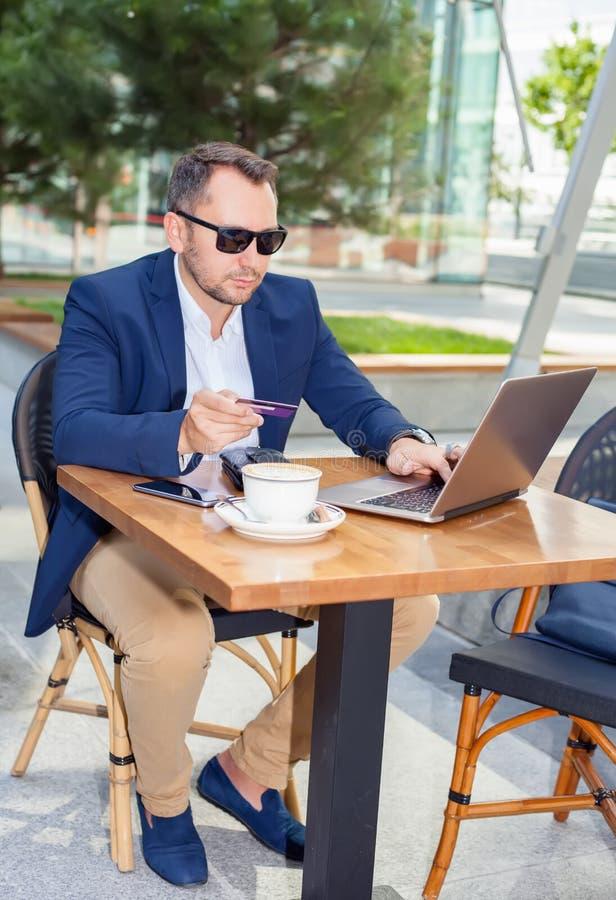 Affärsman som arbetar på bärbara datorn, för att betala vid kreditkorten royaltyfria bilder