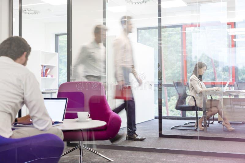 Affärsman som arbetar på bärbara datorn i styrelse med kollegor i bakgrund på kontoret royaltyfri fotografi
