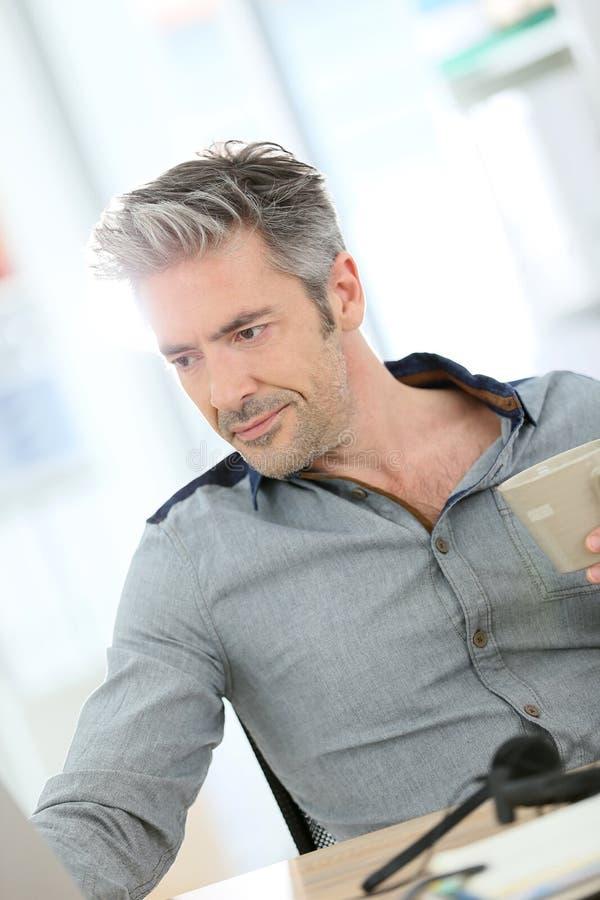 Affärsman som arbetar på bärbara datorn och dricker kaffe arkivbild