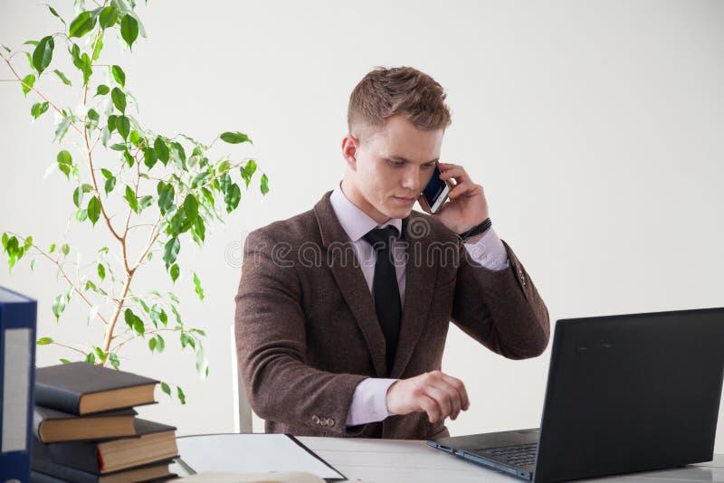 Affärsman som arbetar på datoren och talar på telefonen i kontoret royaltyfri bild