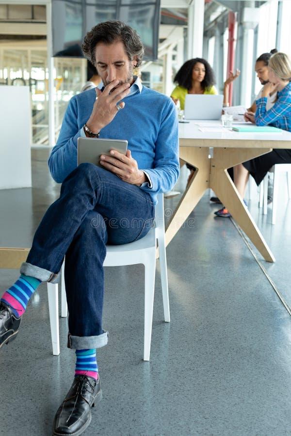Affärsman som arbetar på den digitala minnestavlan på konferensrum i ett modernt kontor royaltyfri fotografi