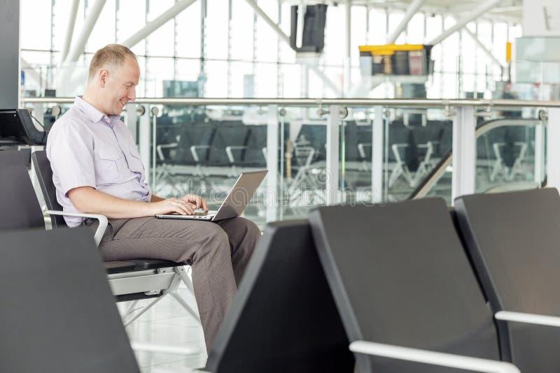 Affärsman som arbetar på flygplatsen under affärslopp royaltyfria bilder