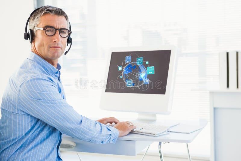 Affärsman som arbetar på hans dator och bärande hörlurar med mikrofon royaltyfri fotografi
