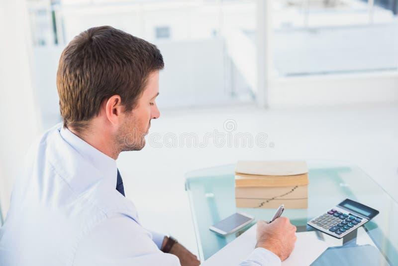 Affärsman som arbetar på hans finanser på hans skrivbord arkivbild