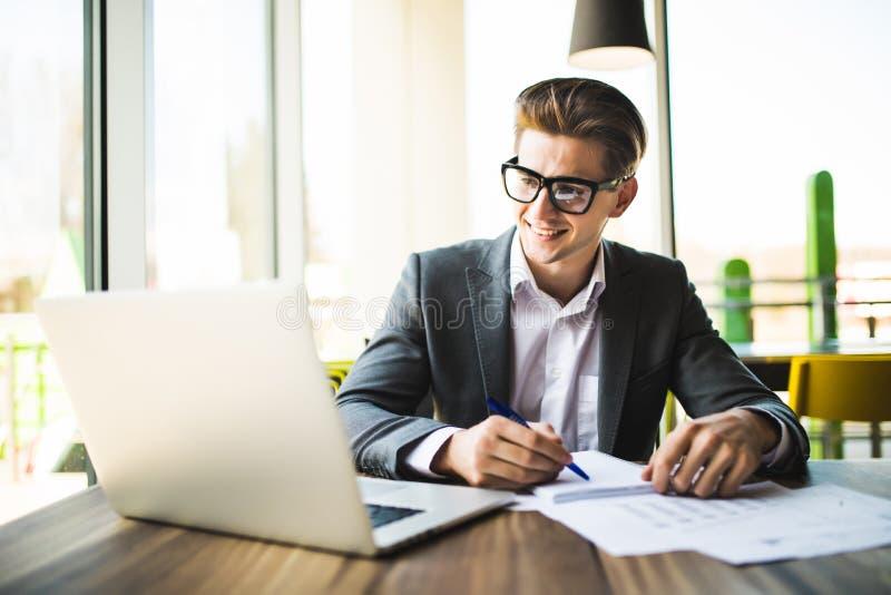 Affärsman som arbetar på kontoret med bärbara datorn och dokument på hans skrivbord royaltyfri fotografi