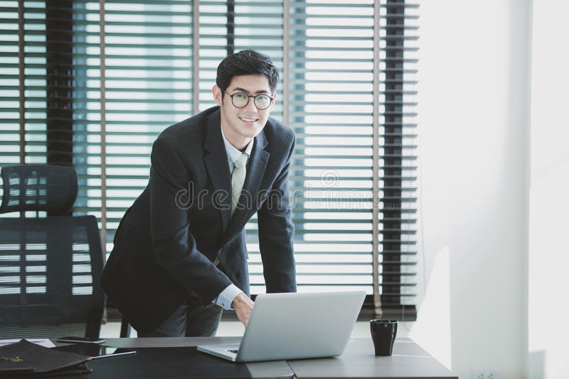 Affärsman som arbetar på kontoret med bärbara datorn på hans skrivbord royaltyfri foto