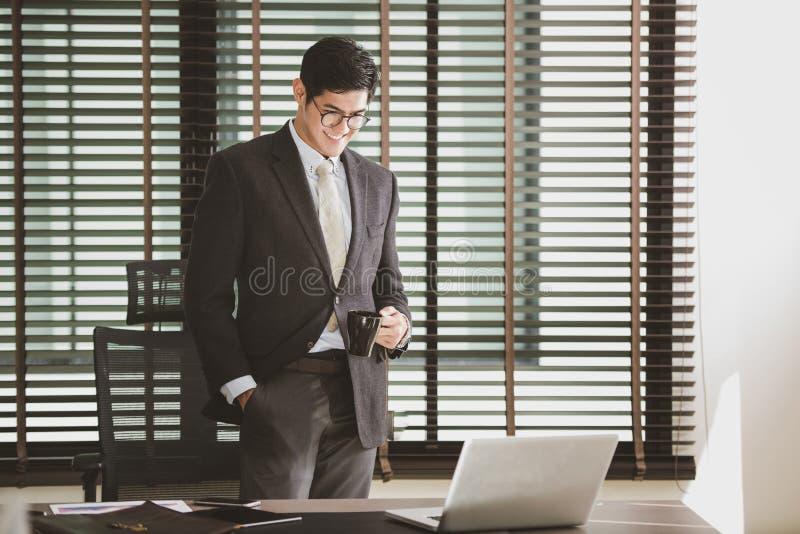 Affärsman som arbetar på kontoret med bärbara datorn på hans skrivbord arkivbild