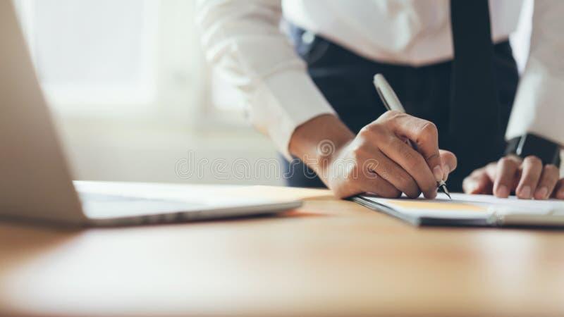 Affärsman som arbetar på kontoret med tecknet ett dokument och en bärbar dator royaltyfri fotografi