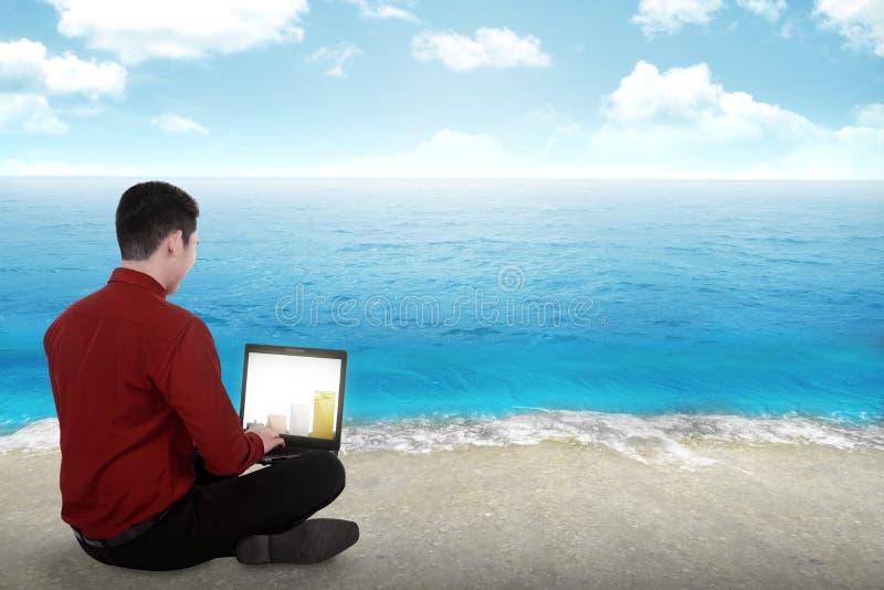 Affärsman som arbetar på stranden royaltyfria foton