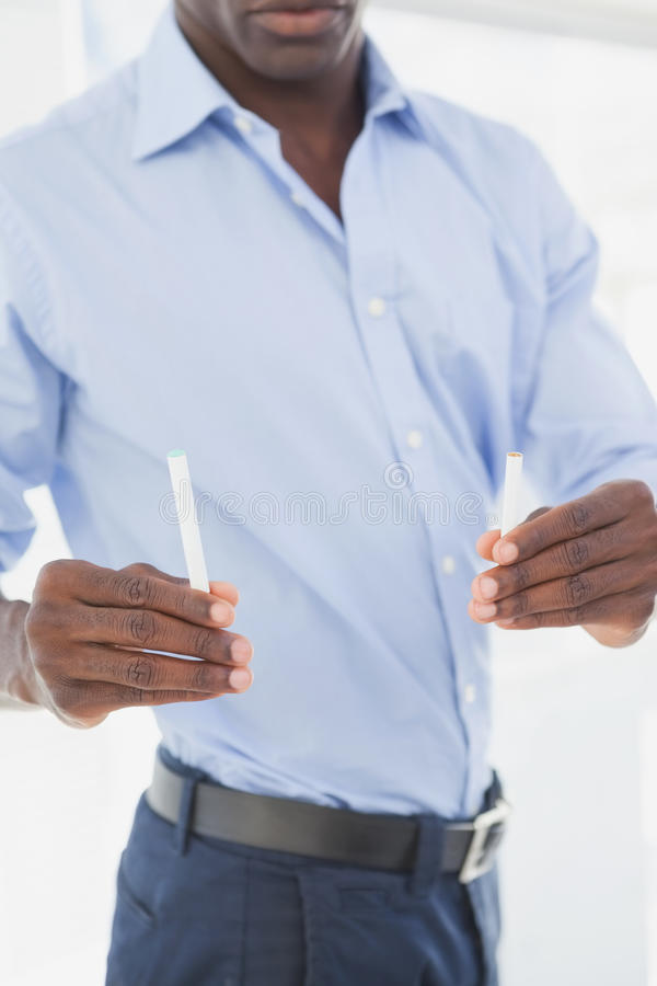 Affärsman som avgör mellan den elektroniska eller normala cigaretten royaltyfria bilder