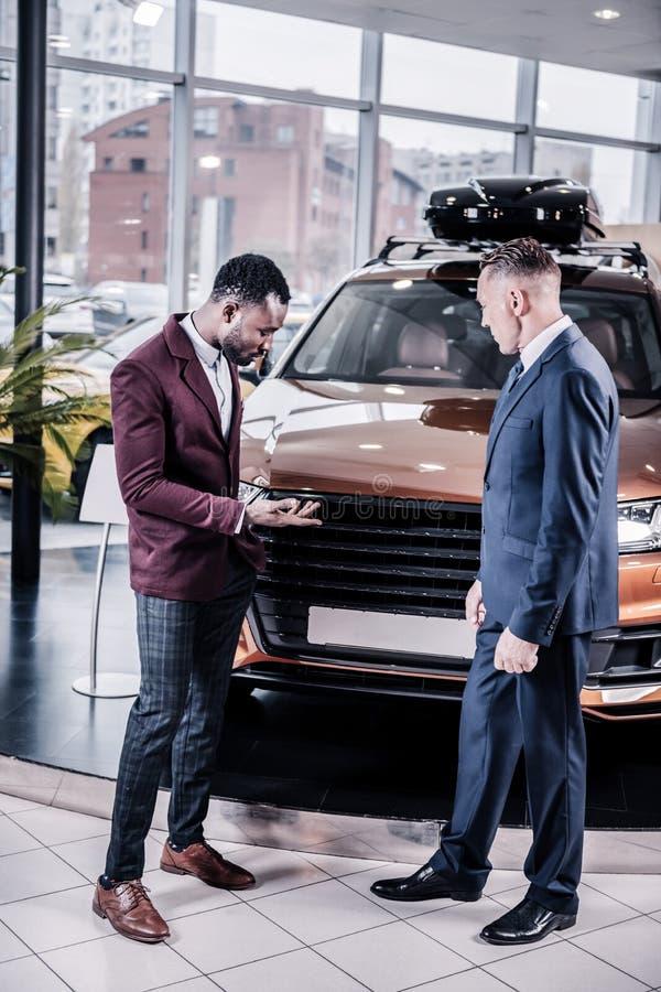 Affärsman som bär kvadrerad byxa som frågar frågor om bilen royaltyfri foto