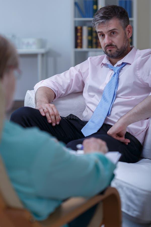 Affärsman som behöver psykologisk terapi arkivfoton