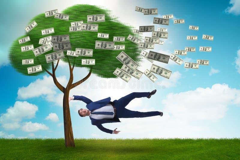 Affärsman som blåsas i väg från pengarträdet arkivbild