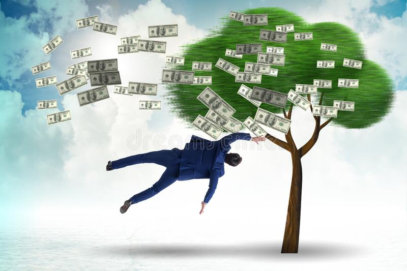 Affärsman som blåsas i väg från pengarträdet arkivfoto