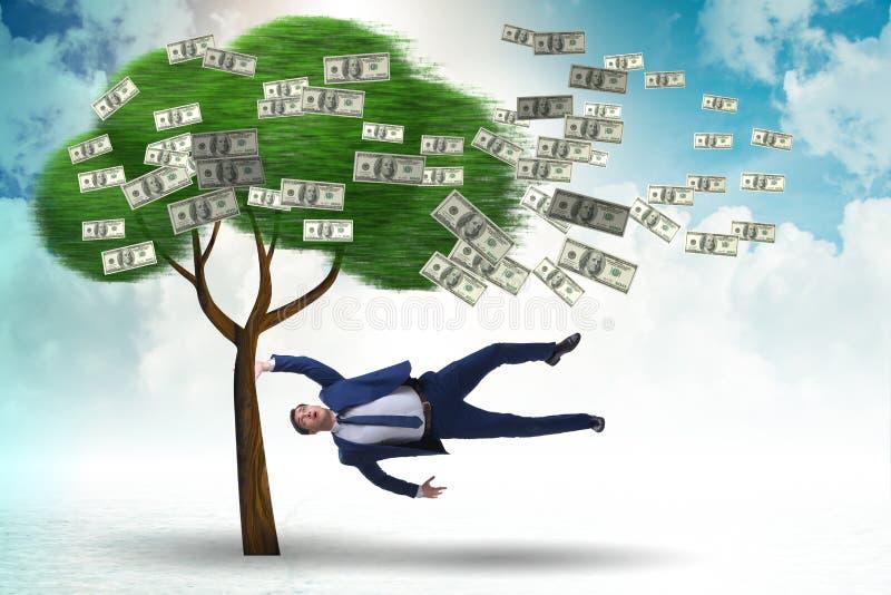Affärsman som blåsas i väg från pengarträdet royaltyfri foto