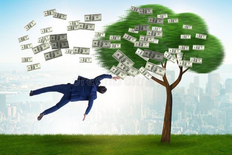 Affärsman som blåsas i väg från pengarträdet royaltyfri bild